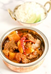 beef curry and potatoes in a dish with red chili peppers on top and a bowl of rice with two green limes