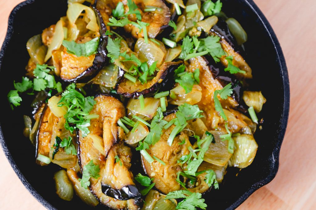 eggplant stir fry with onions, green cilantro in a cast iron skillet